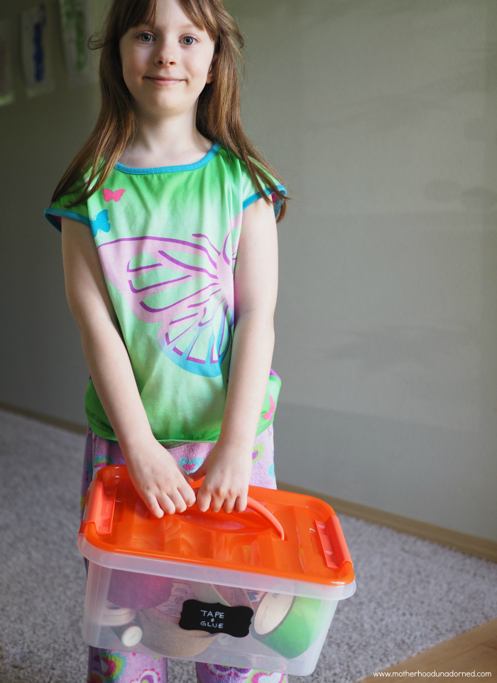6 year old holding Snapware storage container of art supplies