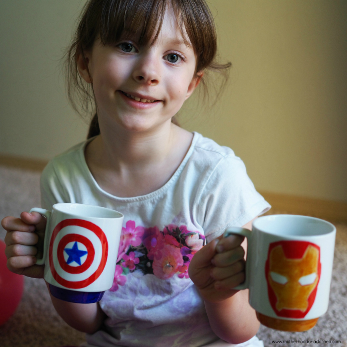 young girl with captain america and ironman mugs