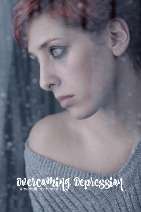 beautiful sad woman behind window at a rainy day depression