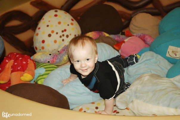 boy playing in stuffed animals